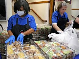 People helping to package food during the Coronavirus crisis as school food services are disrupted. Photo Credit: JSOnline