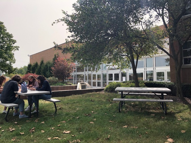 Students gather at a safe distance for lunch in front of school. With hybrid learning, there usually is plenty of space at the tables.