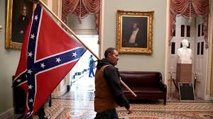 Man carries the Confederate flag through the halls of Congress Photo Credit: Saul Loeb